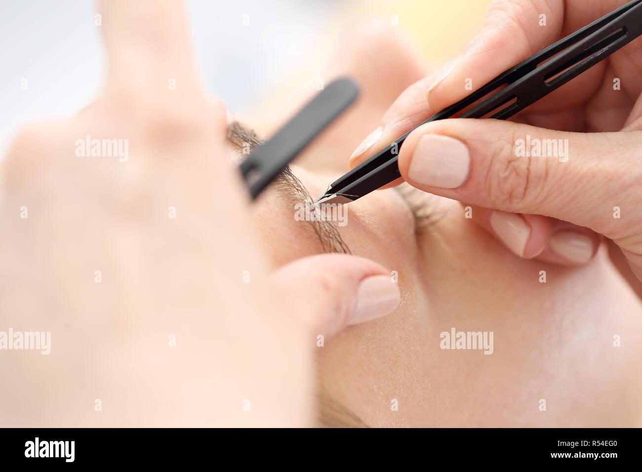 eyebrow tweezers. hair removal. adjusting the eyebrows in the beauty salon. henna and eyebrow adjustment. eyebrow styling - Stock Image