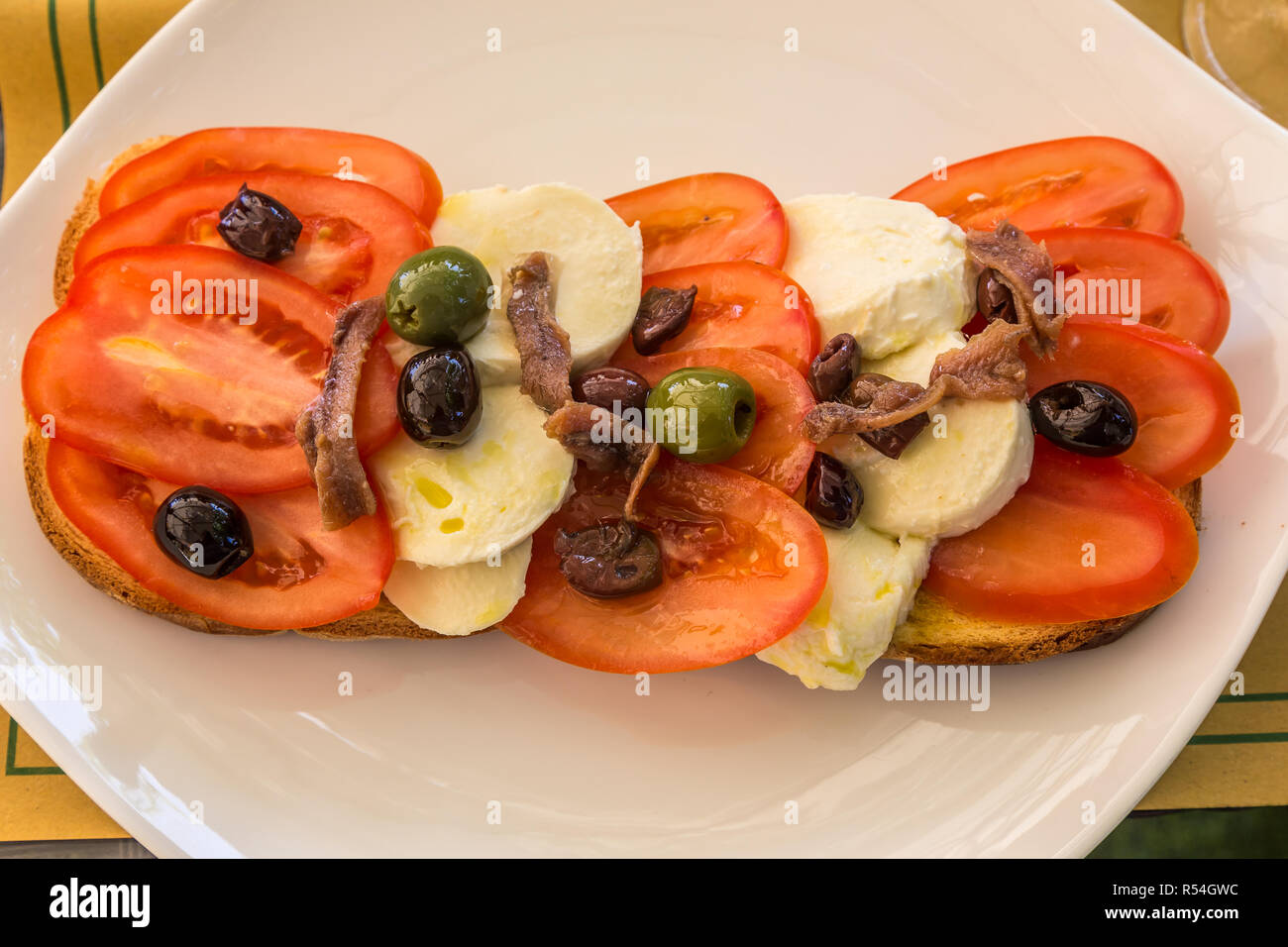 Lunchtime snack of tomatoes, cheese. anchovies and olives on bread, served on a white plate. - Stock Image