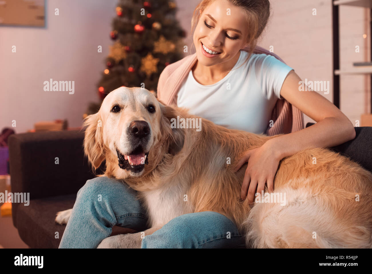 Beautiful Smiling Young Blonde Woman Sitting On Couch And Hugging