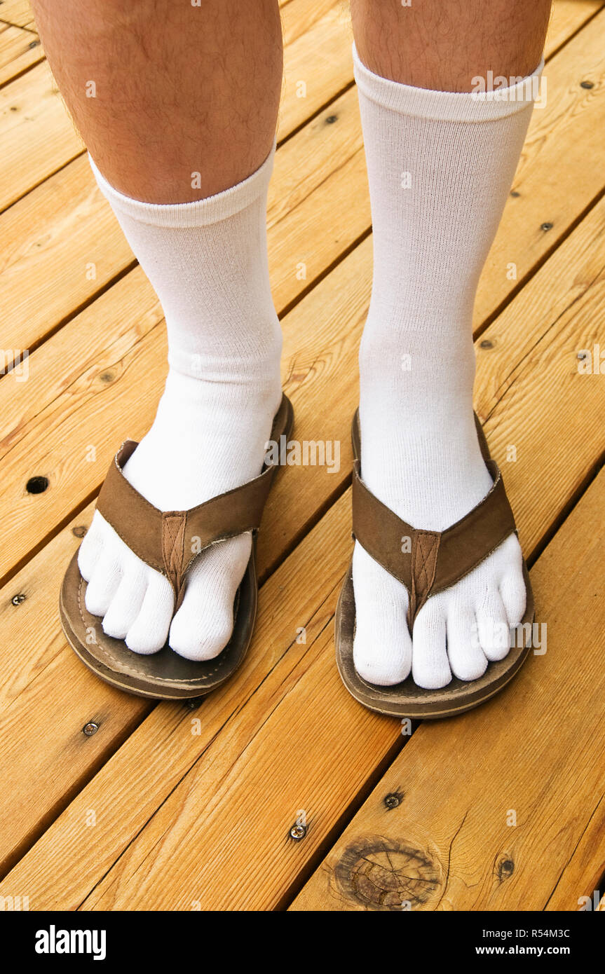 A man wearing flip flops with socks - Stock Image