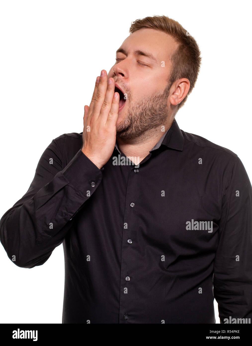 Portrait of caucasian yawning man. He is exhausted and tired because of a lot of work. Studio portrait on white background - Stock Image