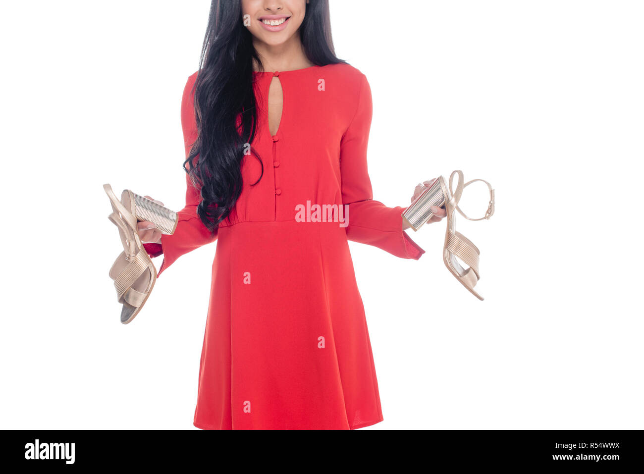 7526e638a847 partial view of african american girl in red dress holding sandals with  heels isolated on white