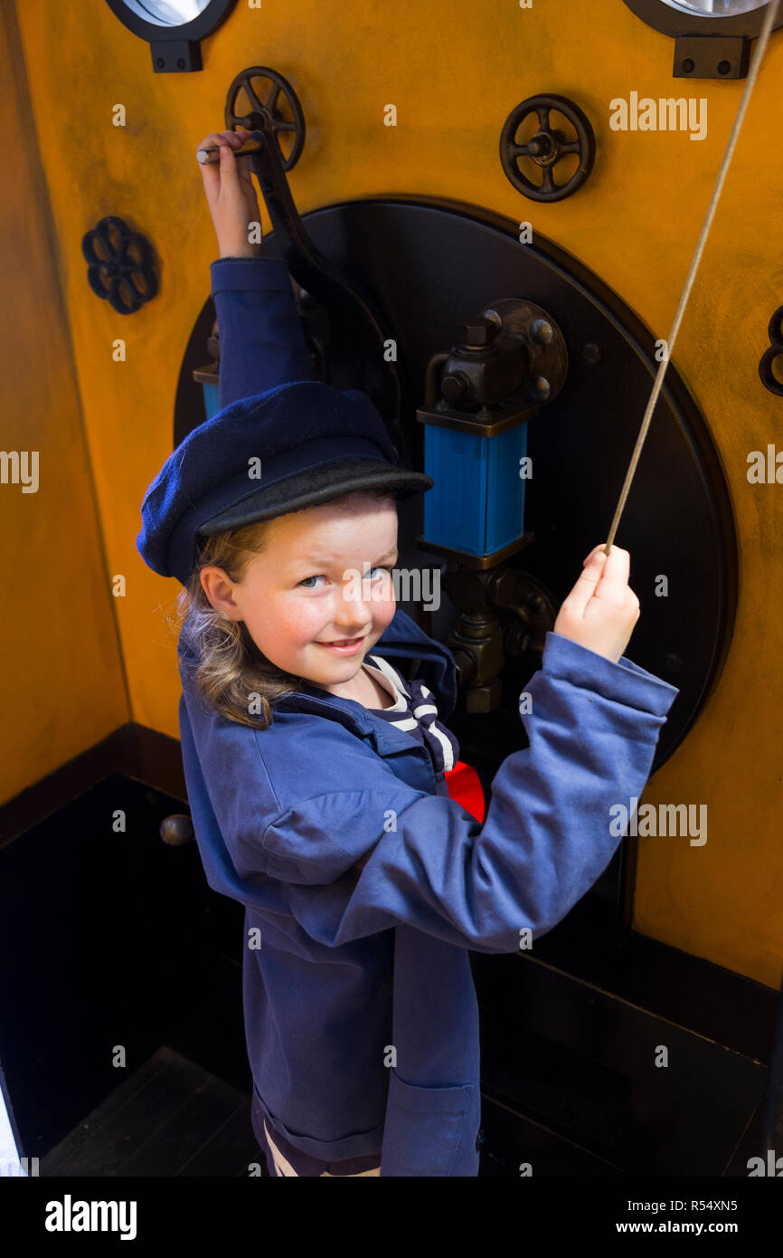 Young girl aged six years old acting / playing being a train driver in the Train Story museum play area at Havenstreet / Haven street station on the on the Isle of Wight steam Railway. UK (98) - Stock Image