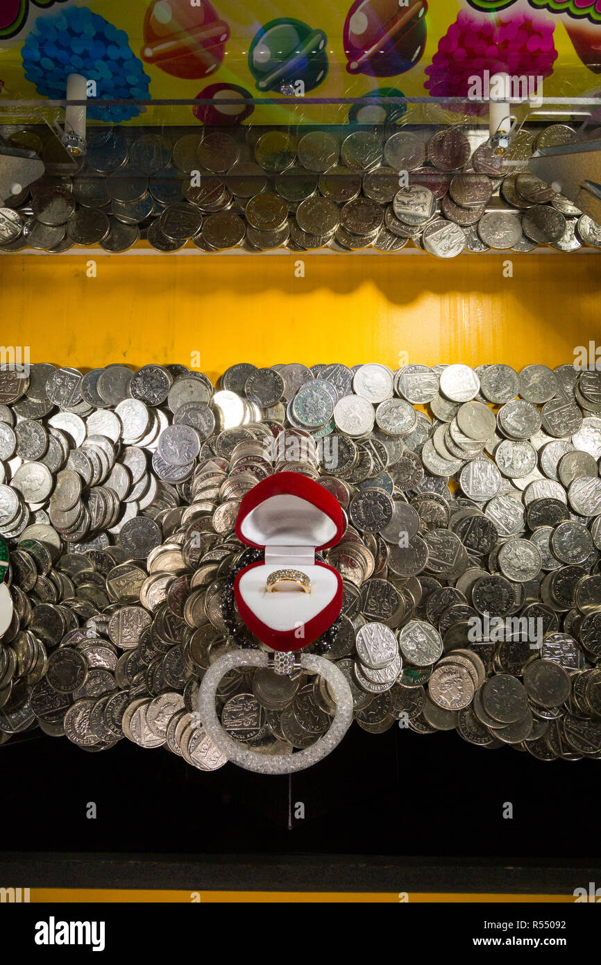 Coins waiting to fall and be won ( or lost and go to the arcade proprietor ) in a traditional coin pusher / pushing coins game at a pier fun house arcade. UK. (98). - Stock Image