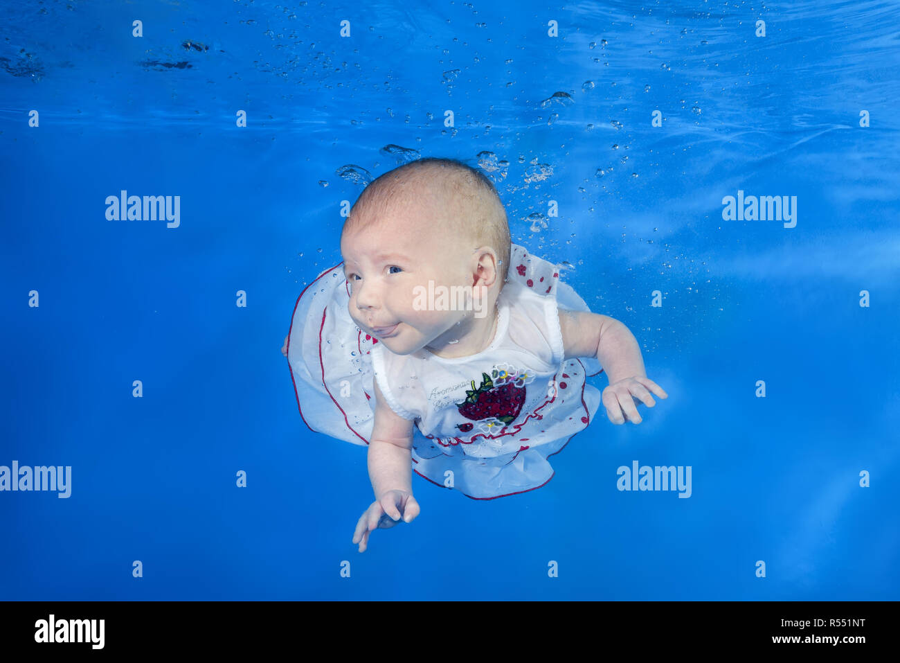 1.5 months girl in a white dress swims underwater in the pool on a blue water background. Healthy family lifestyle and children water sports activity. - Stock Image