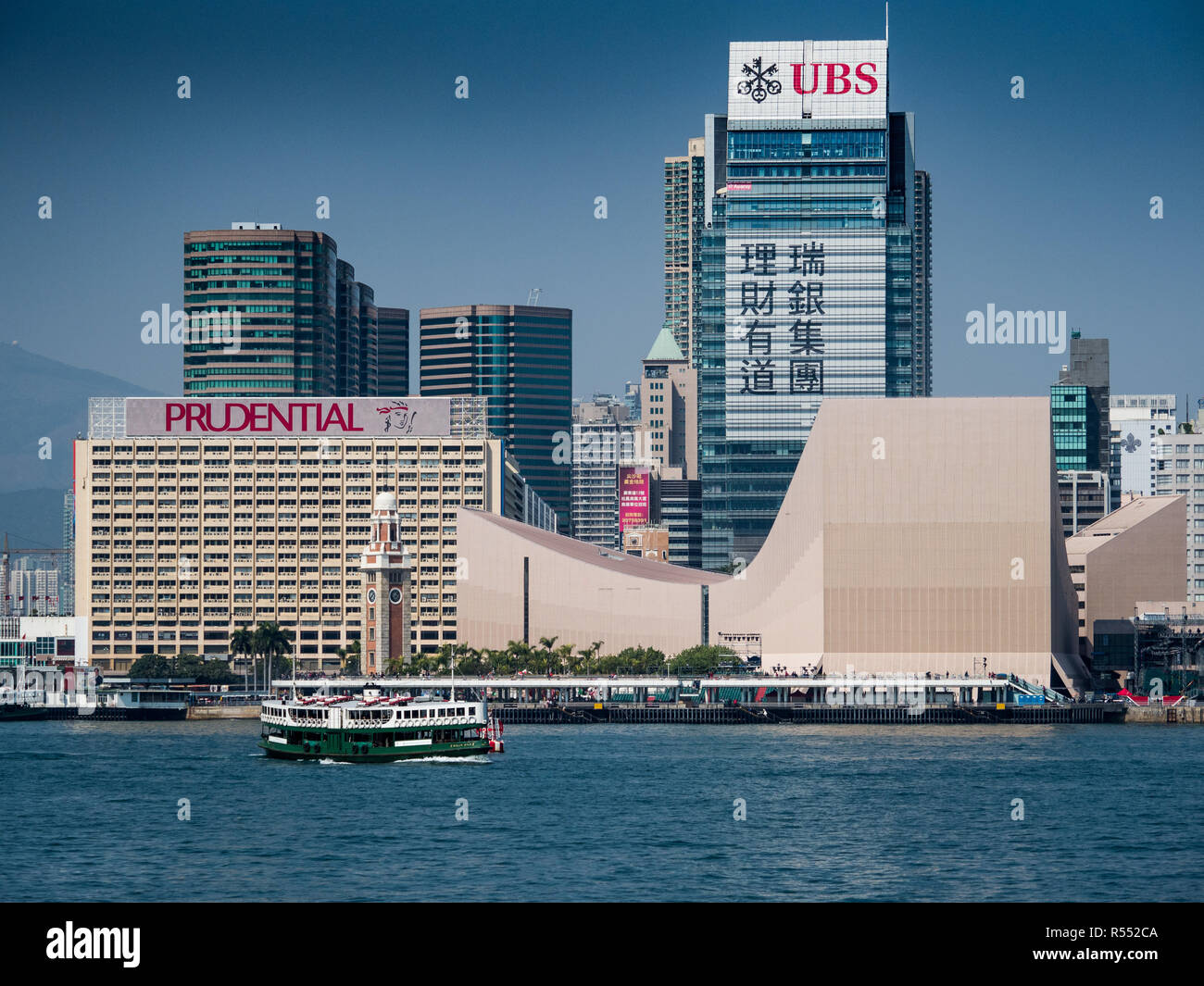 Hong Kong - Star Ferry sails in front of large UBS and Prudential adverts on the Kowloon side of Victoria Harbour - Stock Image