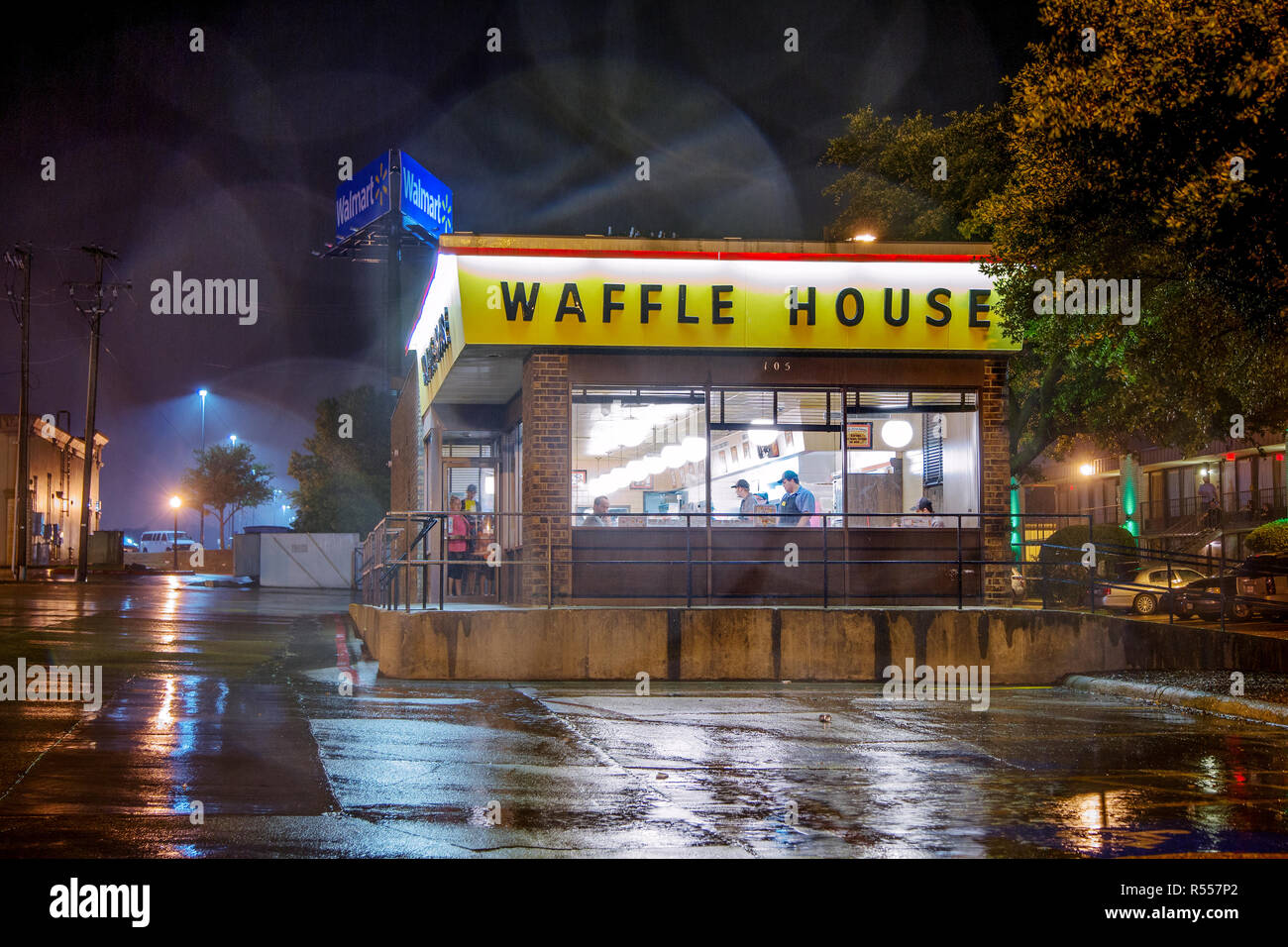Patrons at a local Waffle House eat their greasy spoon fast food while rain is pouring down outside. - Stock Image