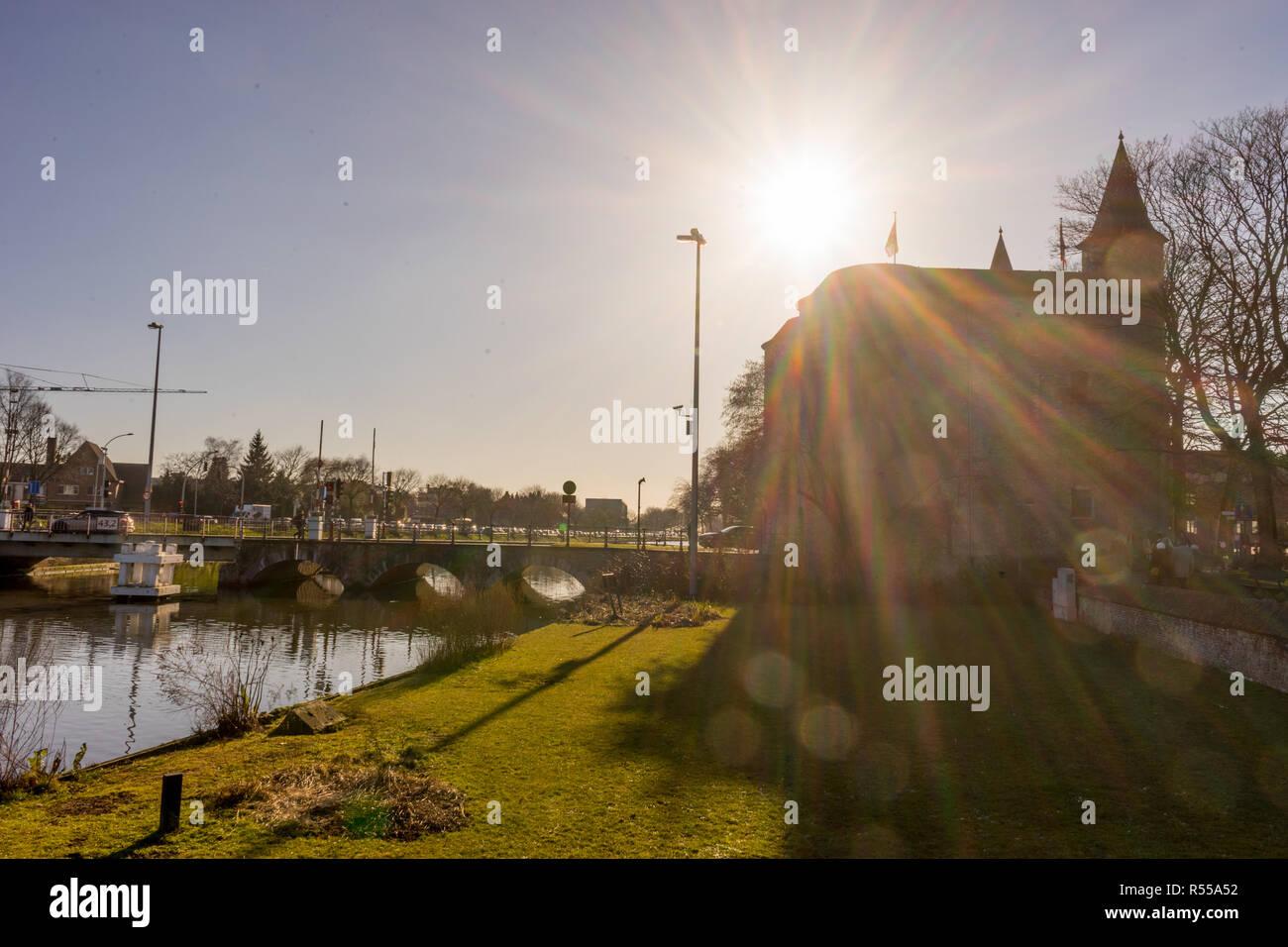 Bruges, Belgium - 17 February 2018: Sun shining over Gentpoort in Bruges, Belgium Stock Photo
