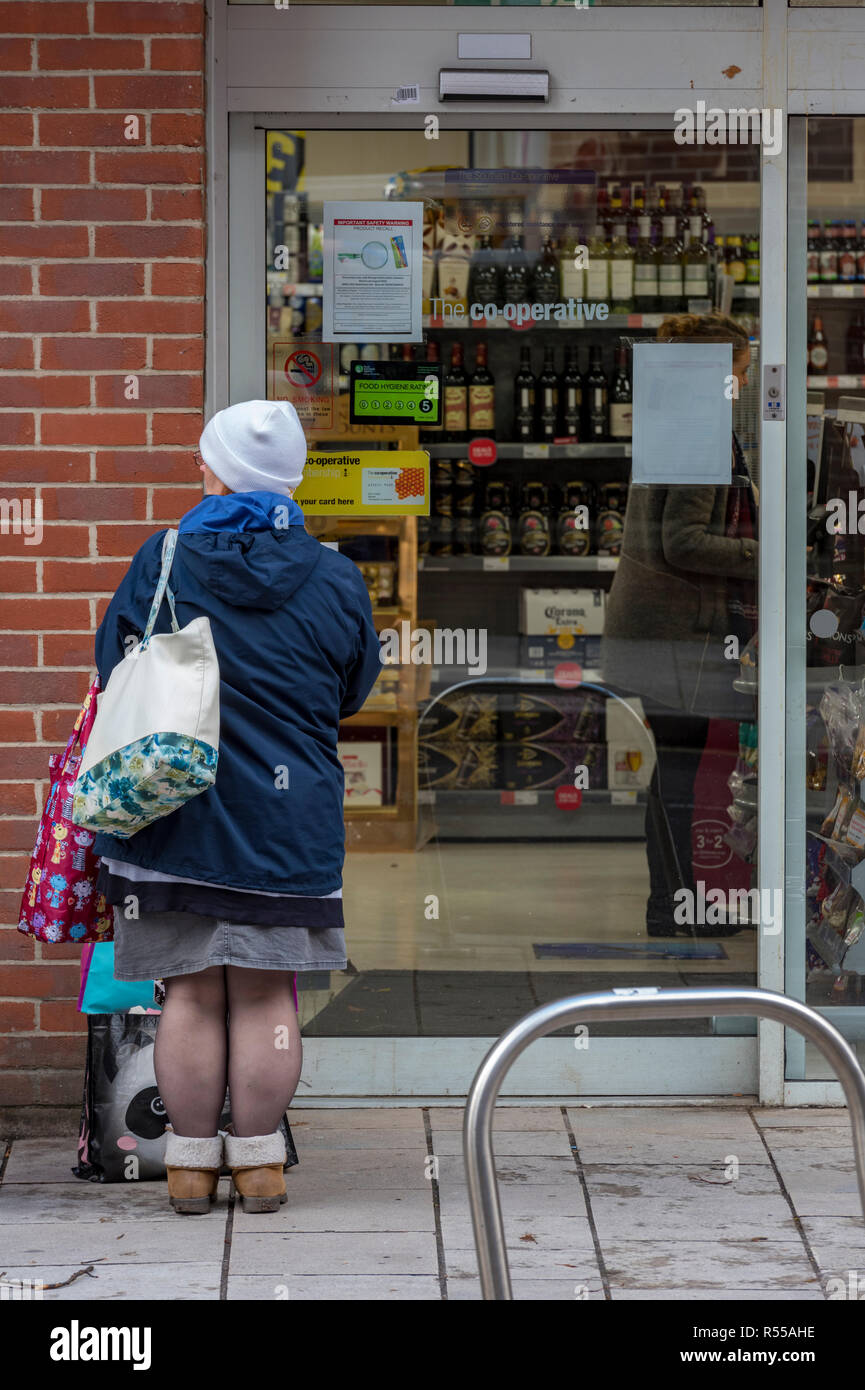 an old lady carrying a shopping bag standing outside of a supermarket looking in the window of the shop. - Stock Image