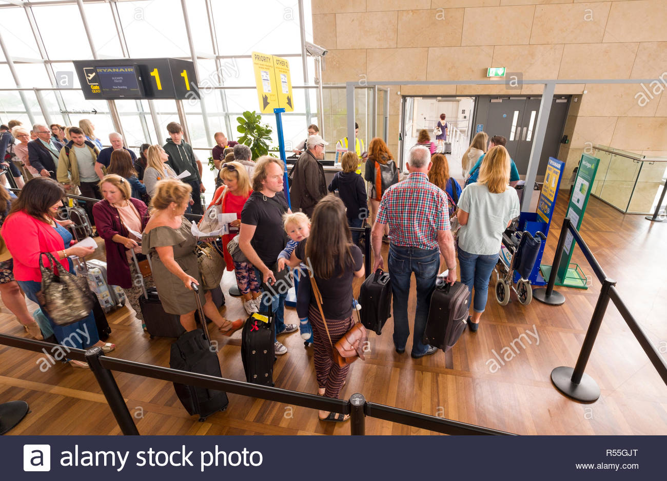 Passengers standing in line in departure lounge waiting to board aircraft at the Cork Airport, Lehenagh More, County Cork, Munster, Ireland - Stock Image