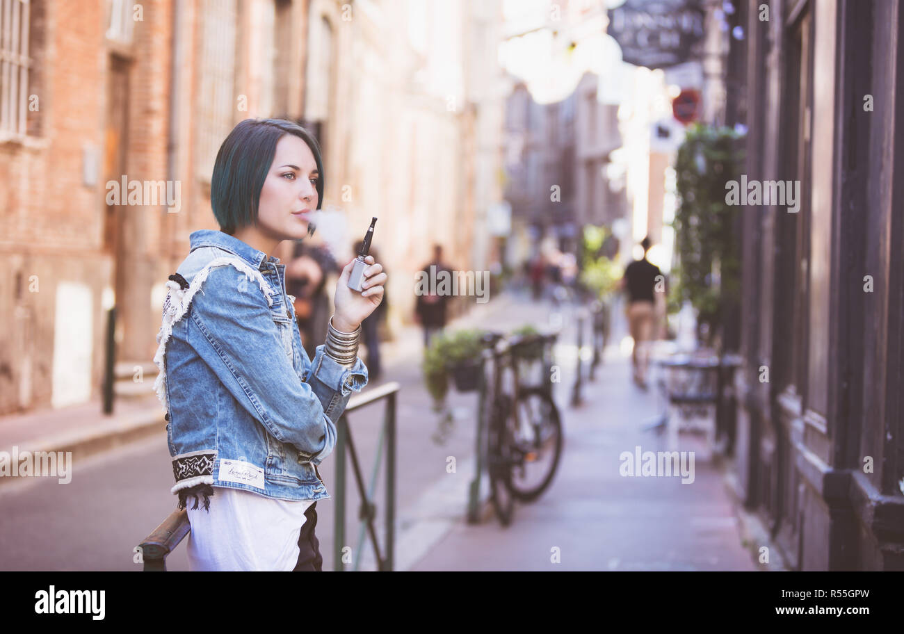 Portrait of a young woman smoking an electronic cigarette in the street - Stock Image