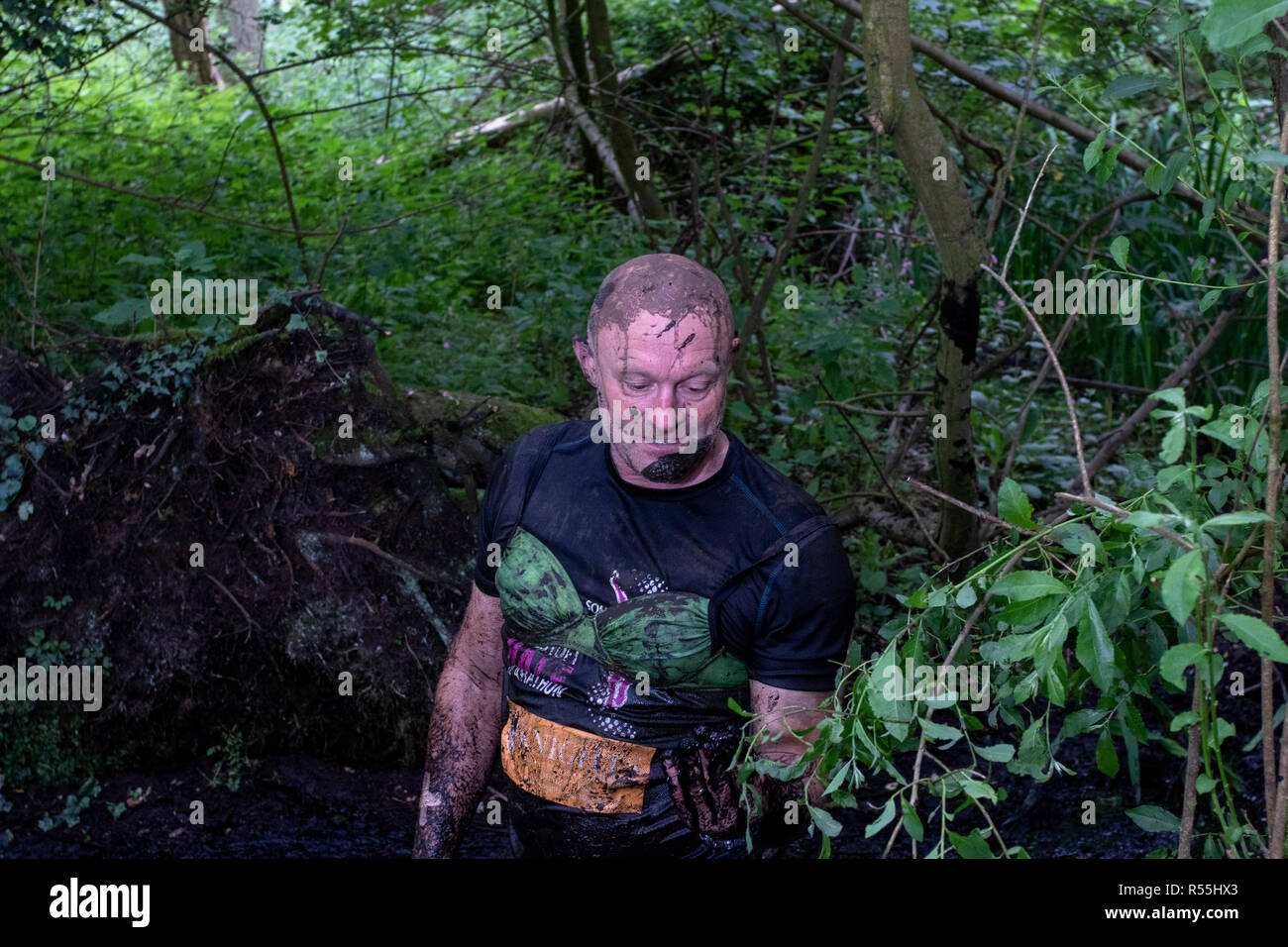 Mud covered male runner wearing a green brassiere - Stock Image