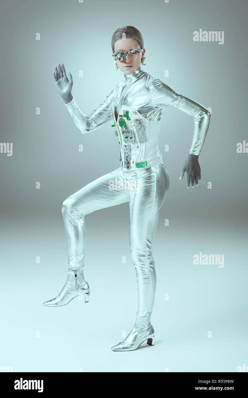 full length view of futuristic cyborg walking and looking at camera on grey, future technology concept - Stock Image