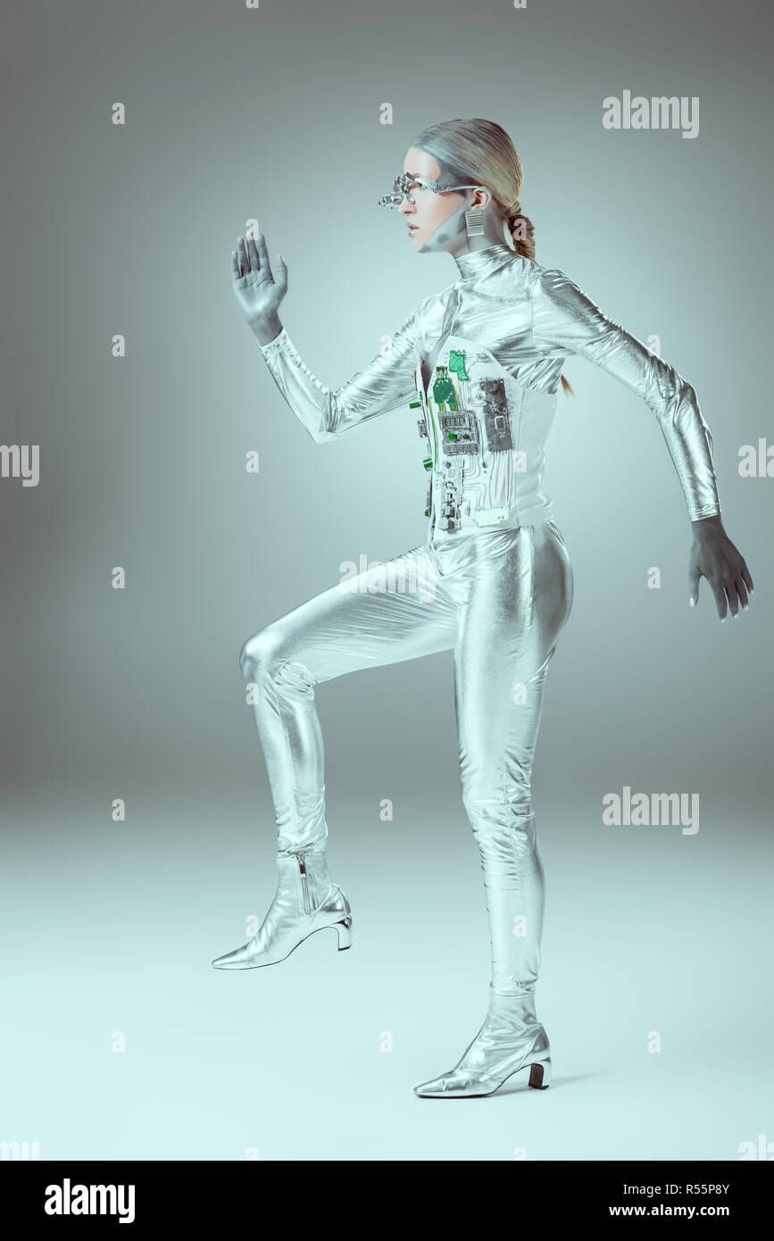side view of futuristic cyborg walking on grey, future technology concept - Stock Image