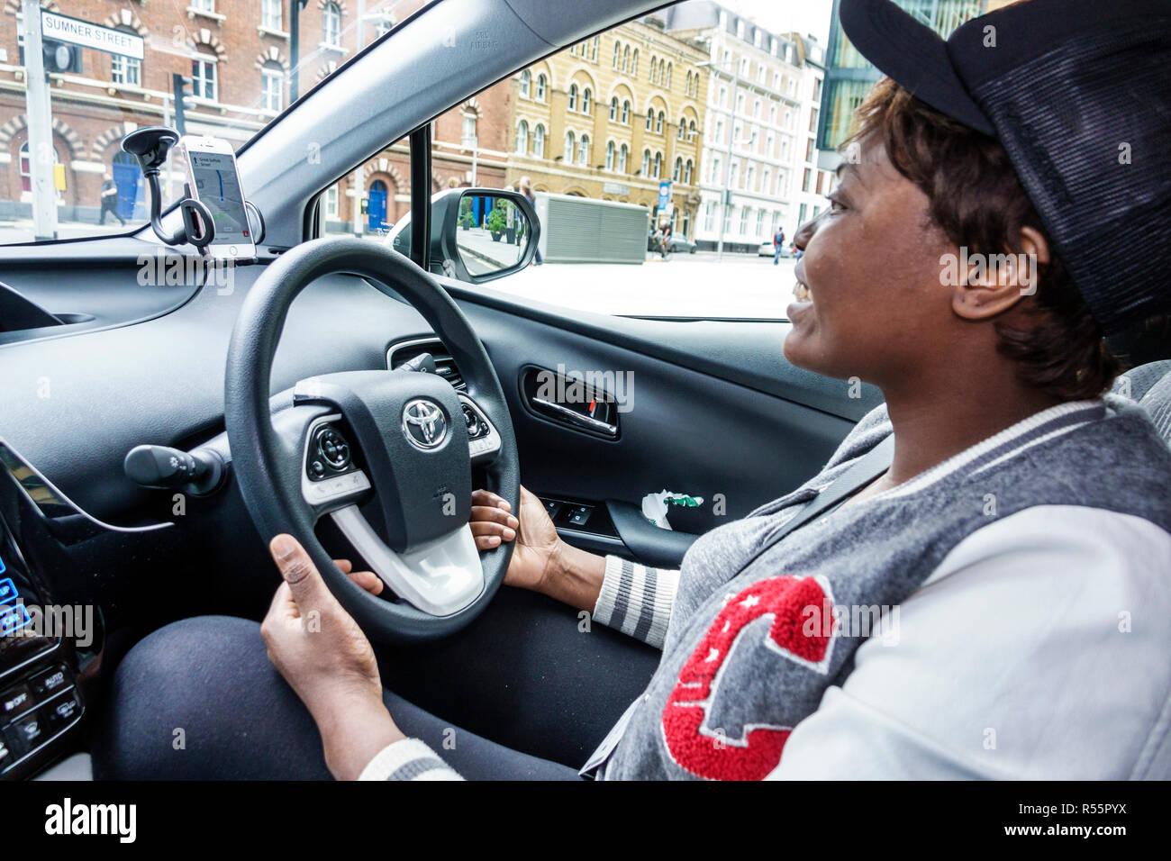 United Kingdom Great Britain England London Southwark uber driver driving car interior inside steering wheel Black woman working - Stock Image
