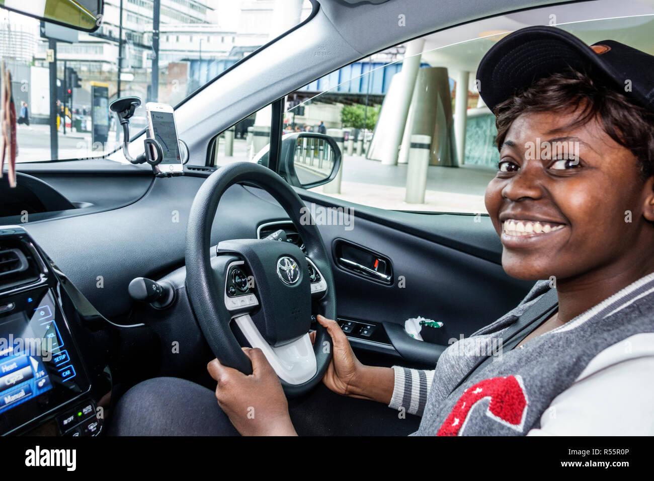 United Kingdom Great Britain England London Southwark uber driver driving car interior inside steering wheel Black woman smiling working - Stock Image