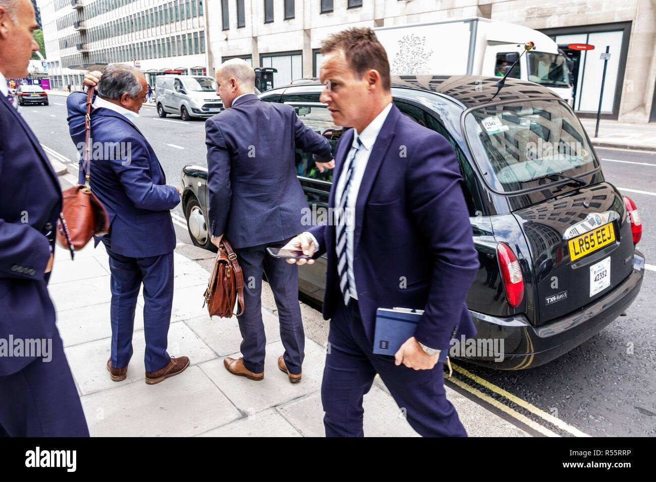 United Kingdom Great Britain England London Westminster black taxicab taxi hackney carriage man businessman dropping off - Stock Image
