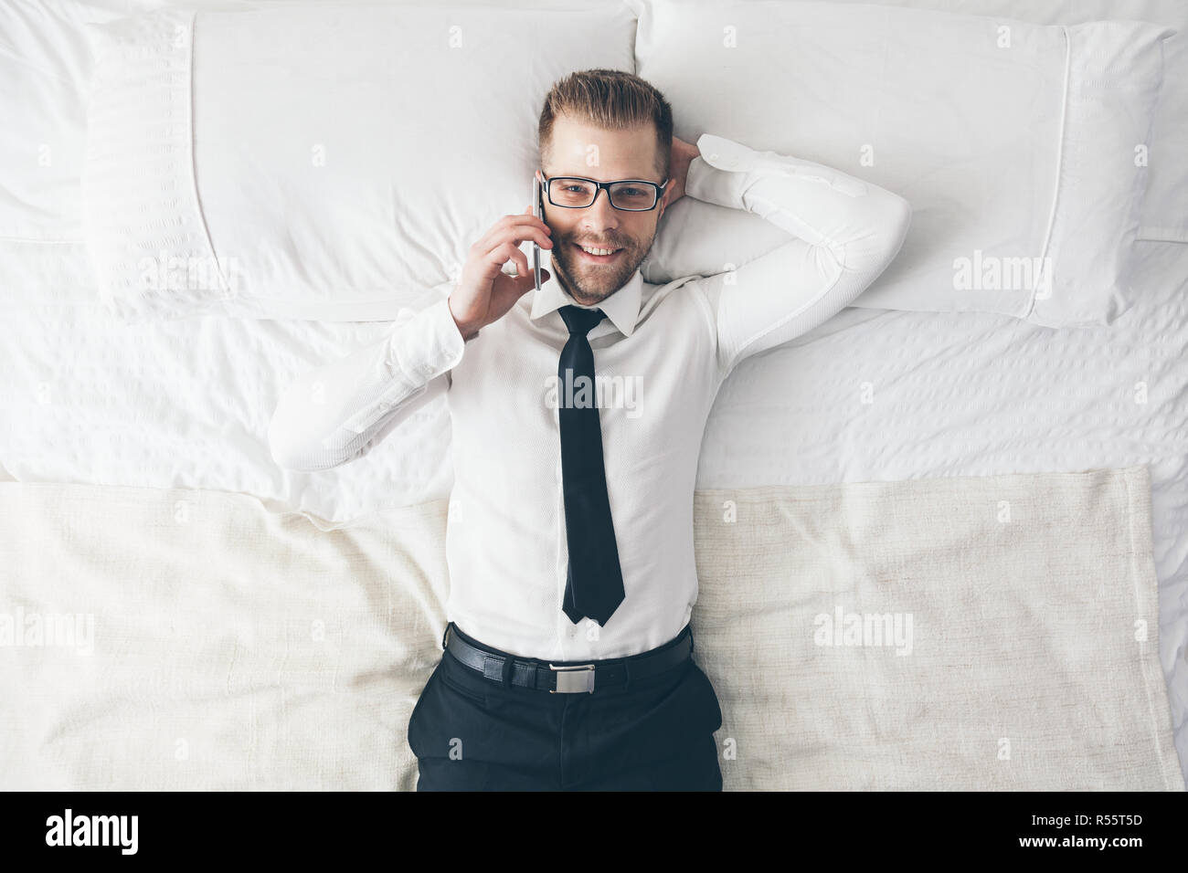 Top view. Handsome businessman with glasses on bed calling from his phone - Stock Image