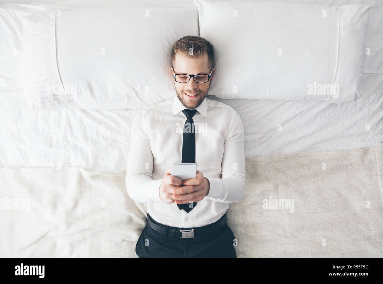 Top view. Handsome businessman with glasses lying on bed texting from his smartphone - Stock Image