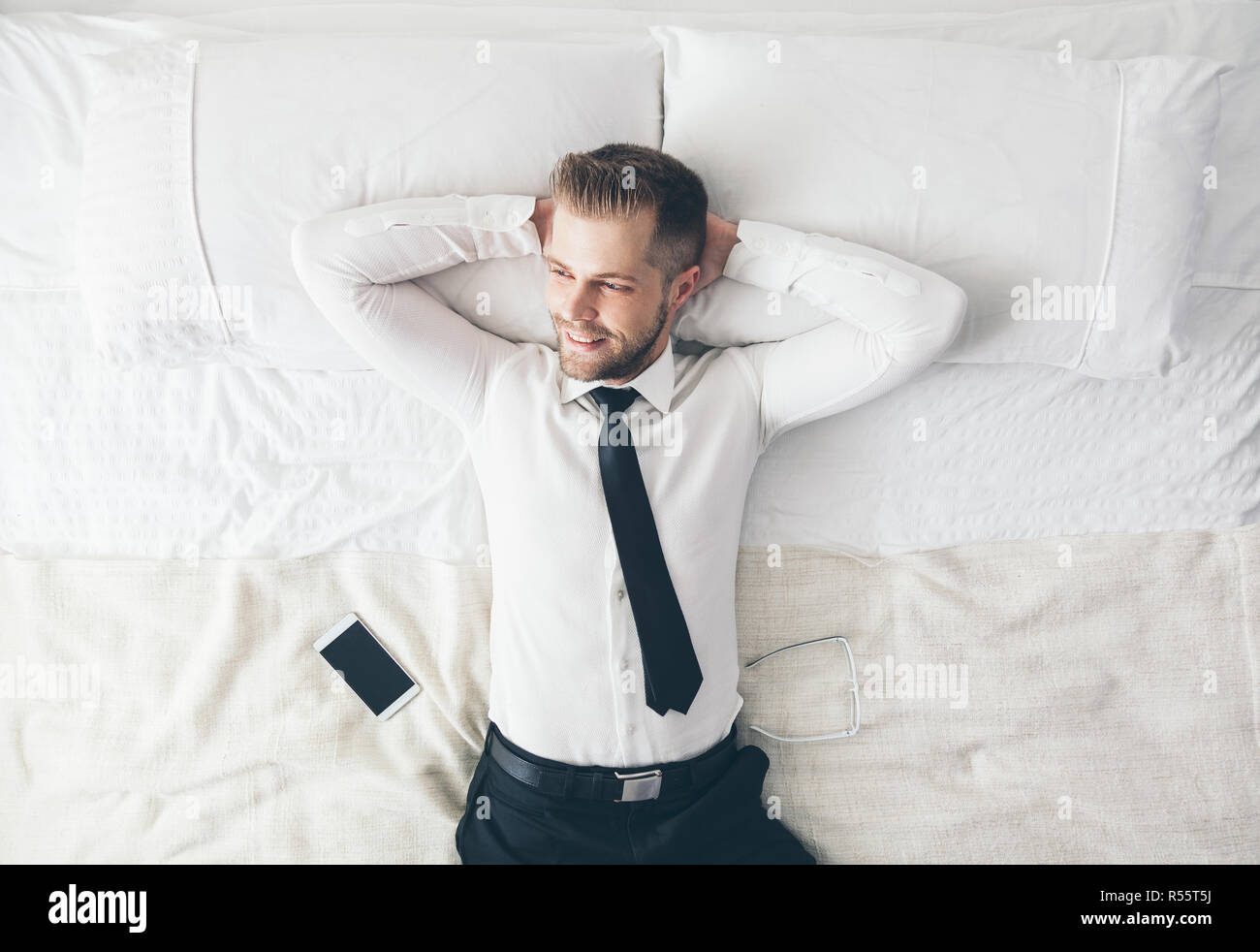 Top view. Handsome businessman relaxing on bed after a tough day at work - Stock Image