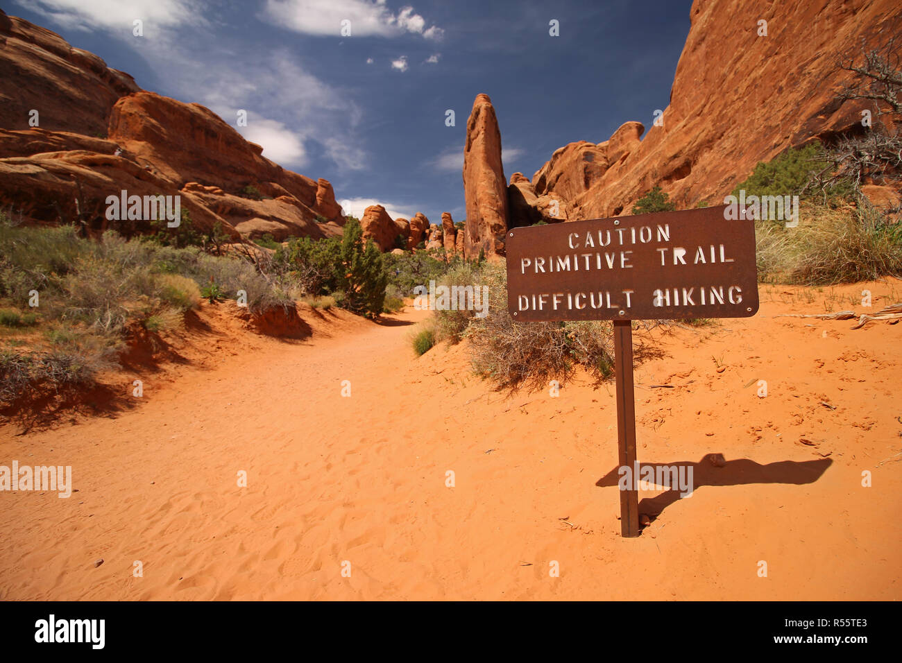 A sign in the desert reads: Caution primitive trail, difficult hiking. - Stock Image