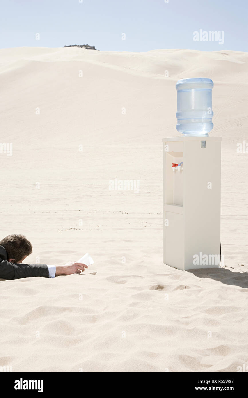 Man by water cooler in the desert - Stock Image