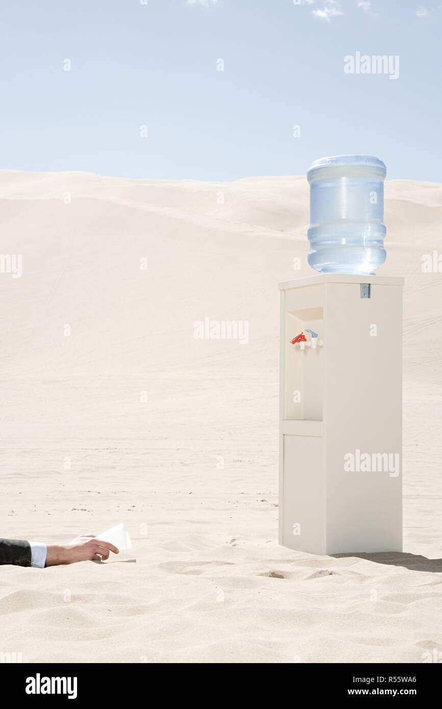 Person reaching for water cooler in desert - Stock Image