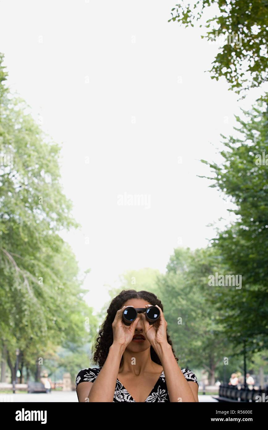 Woman looking through binoculars - Stock Image