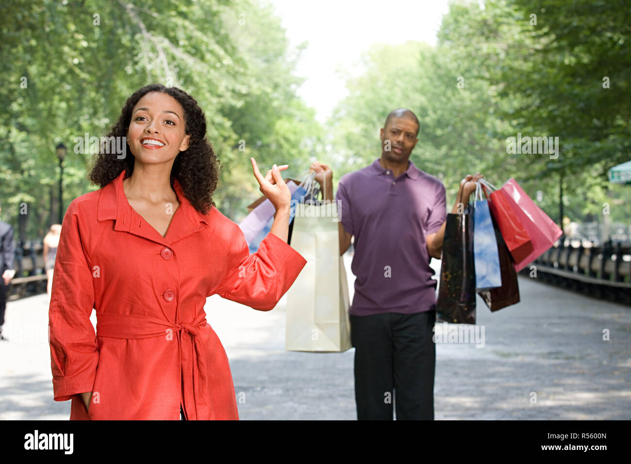 Man holding bags for woman - Stock Image