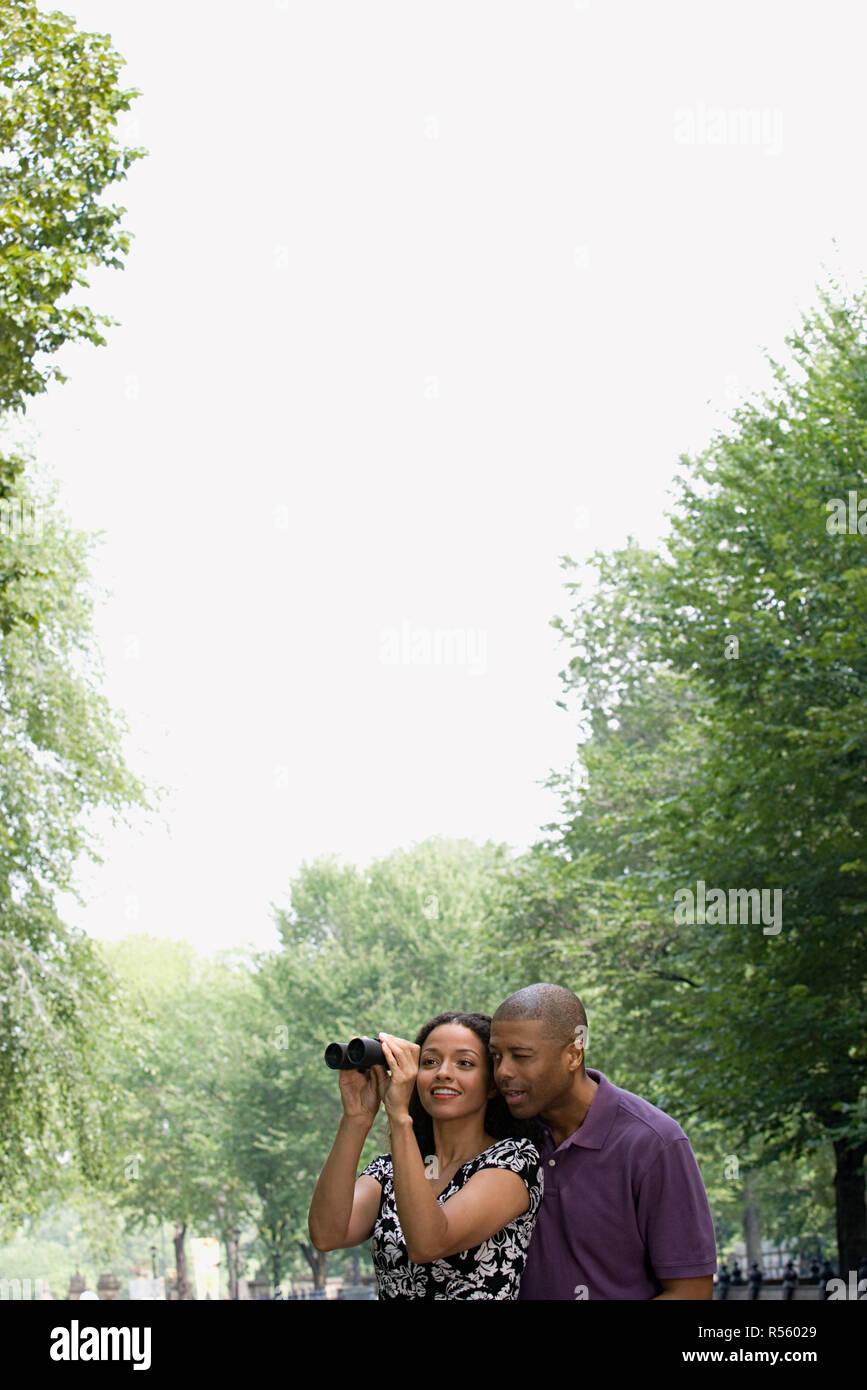 Couple looking through binoculars - Stock Image