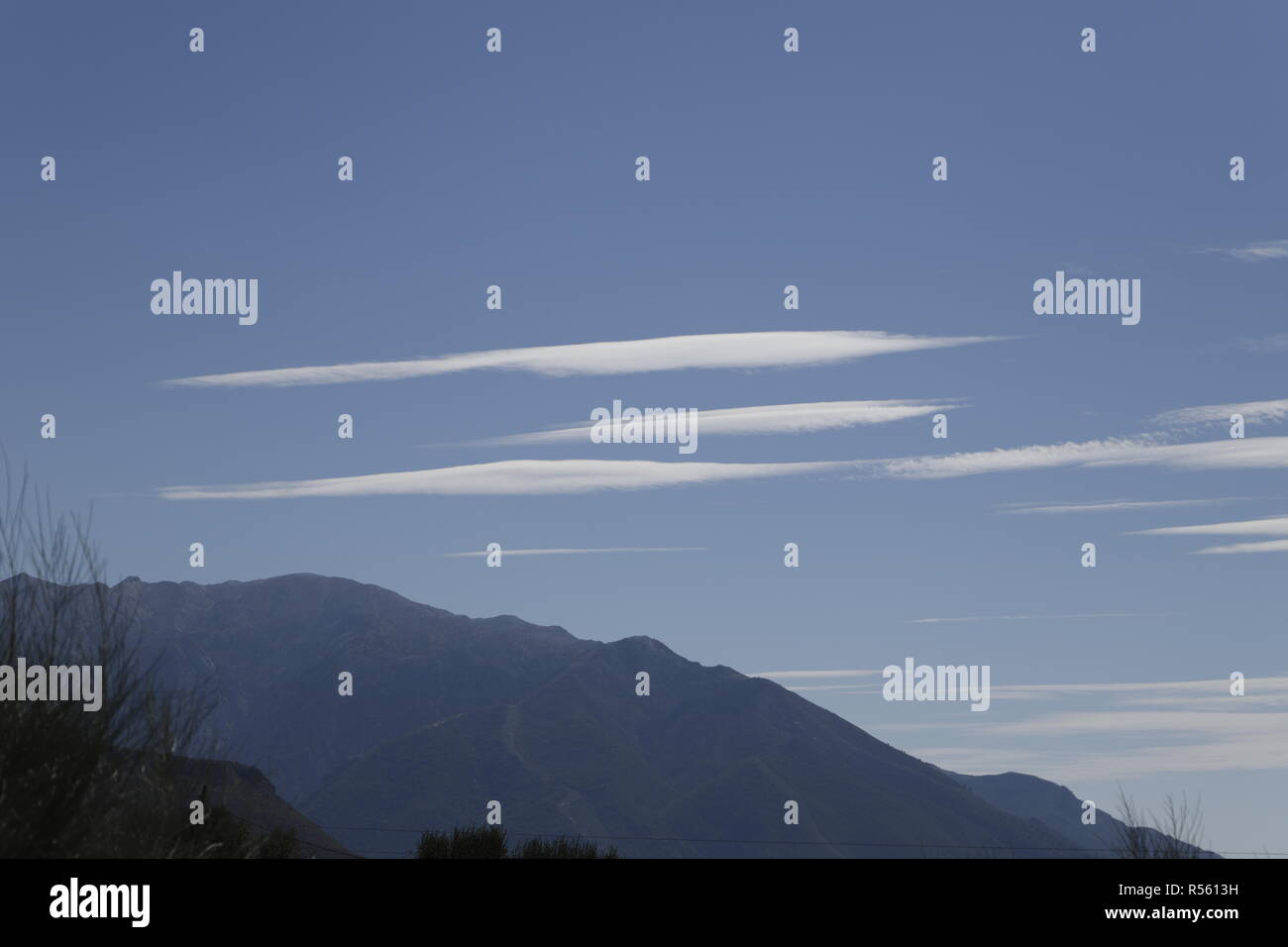Funny flat clouds above the mountains - Stock Image