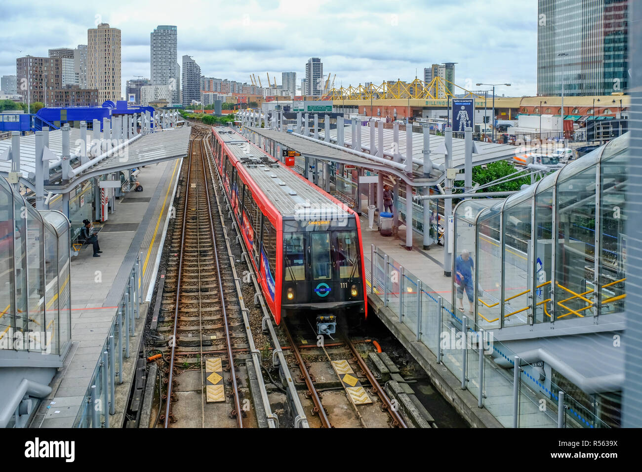 Poplar, London, UK - August 18, 2018: Docklands light railway station at Poplar with a train stopped in the station. - Stock Image