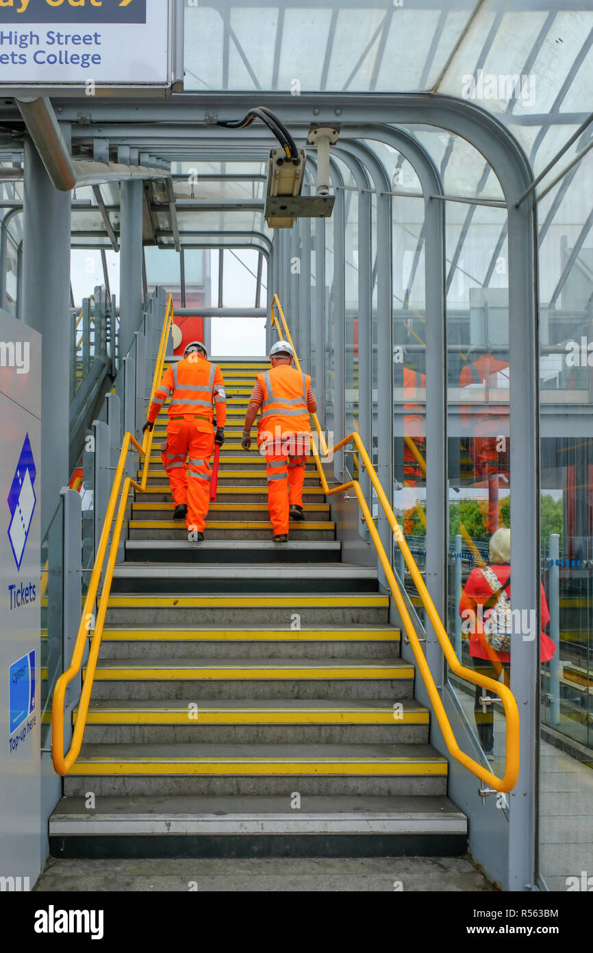 Poplar, London, UK - August 18, 2018: Two workmen dressed in orange hi-viz clothing  and hard hats walking up the stairs at Poplar station. - Stock Image