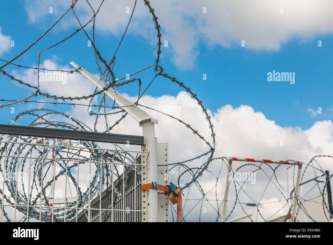 Barbed wire Razor Blades Type Military on blue sky - Stock Image