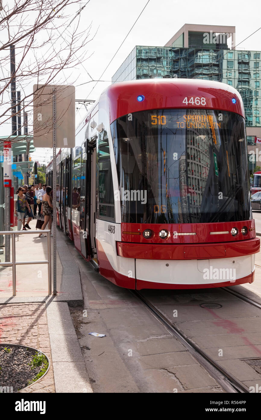 A Flexity Outlook streetcar (number 4468) part of the Spadina line of the TTC (Toronto Transit Commission) running along Queens Quay W. City of Toront - Stock Image