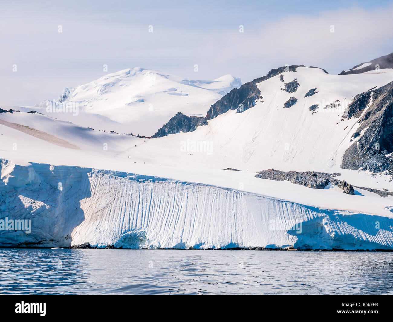 People walking on slope of Spigot Peak on Arctowski peninsula, Antarctic Peninsula, Antarctica Stock Photo