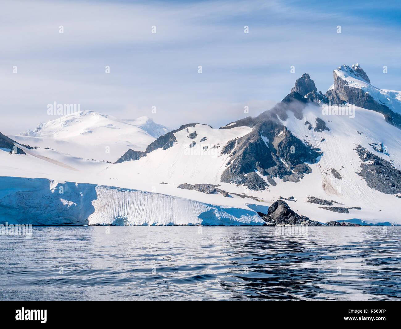 People walking on slope of Spigot Peak on Arctowski peninsula, Antarctic Peninsula, Antarctica Stock Photo