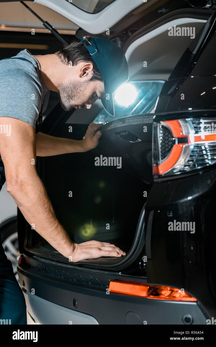 focused auto mechanic checking car trunk at auto repair shop - Stock Image