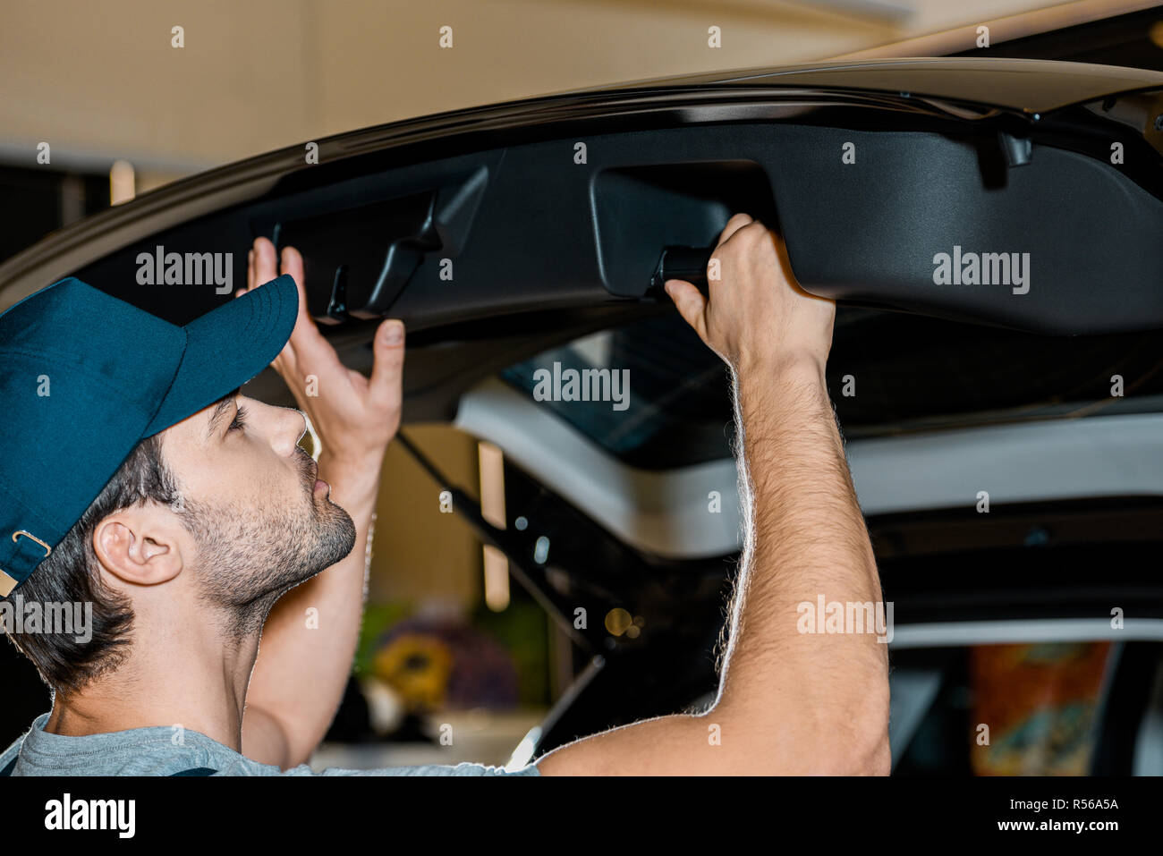 young auto mechanic checking car trunk at auto repair shop - Stock Image