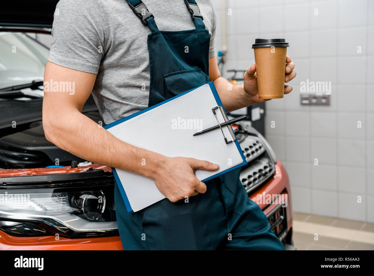 Auto Repair Nearby >> Partial View Of Male Auto Mechanic With Notepad And Coffee