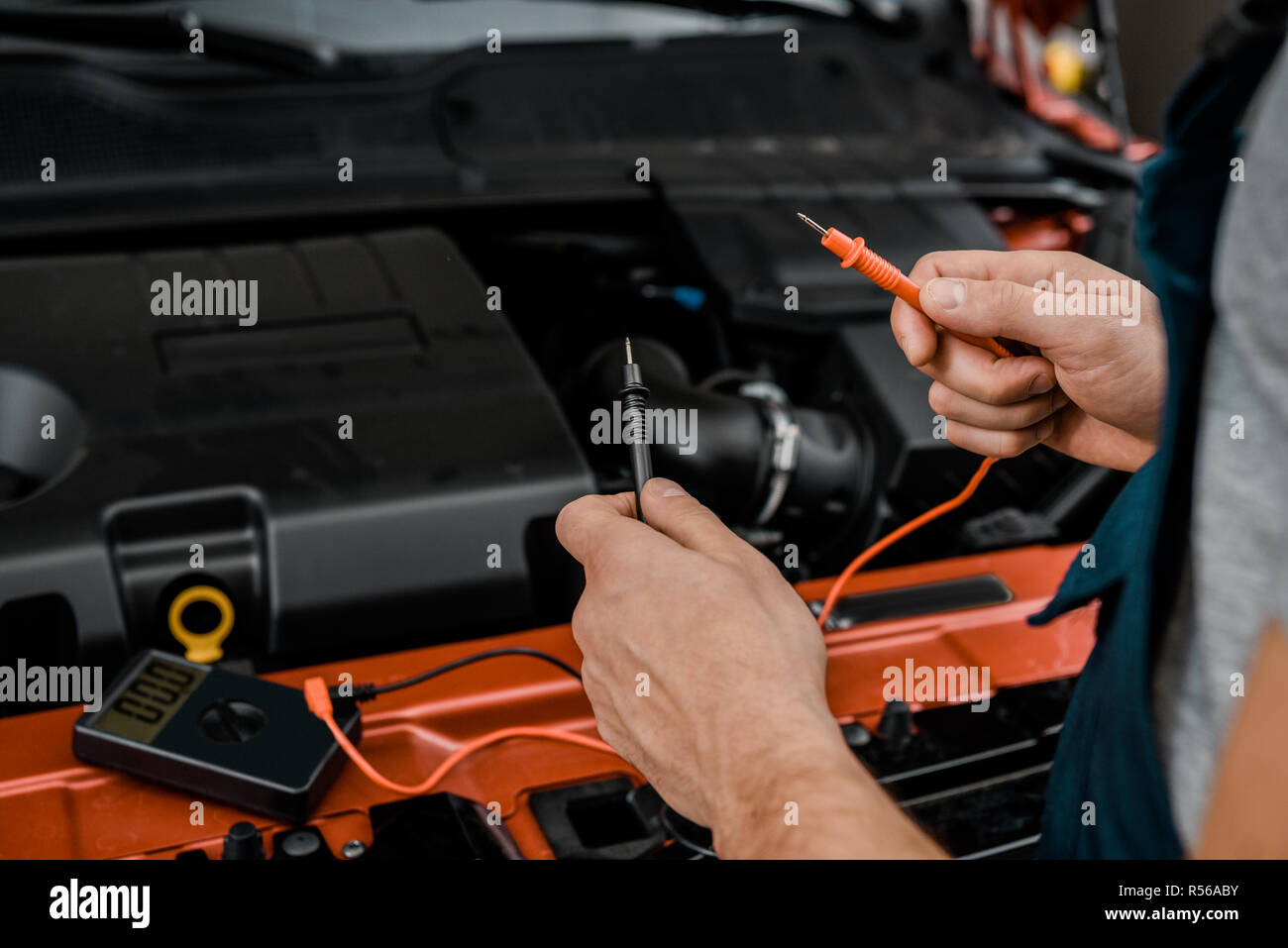 Cropped Shot Of Auto Mechanic With Multimeter Voltmeter Checking Car
