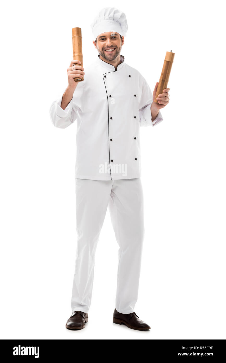 smiling young chef holding bamboo pepper mills isolated on white - Stock Image