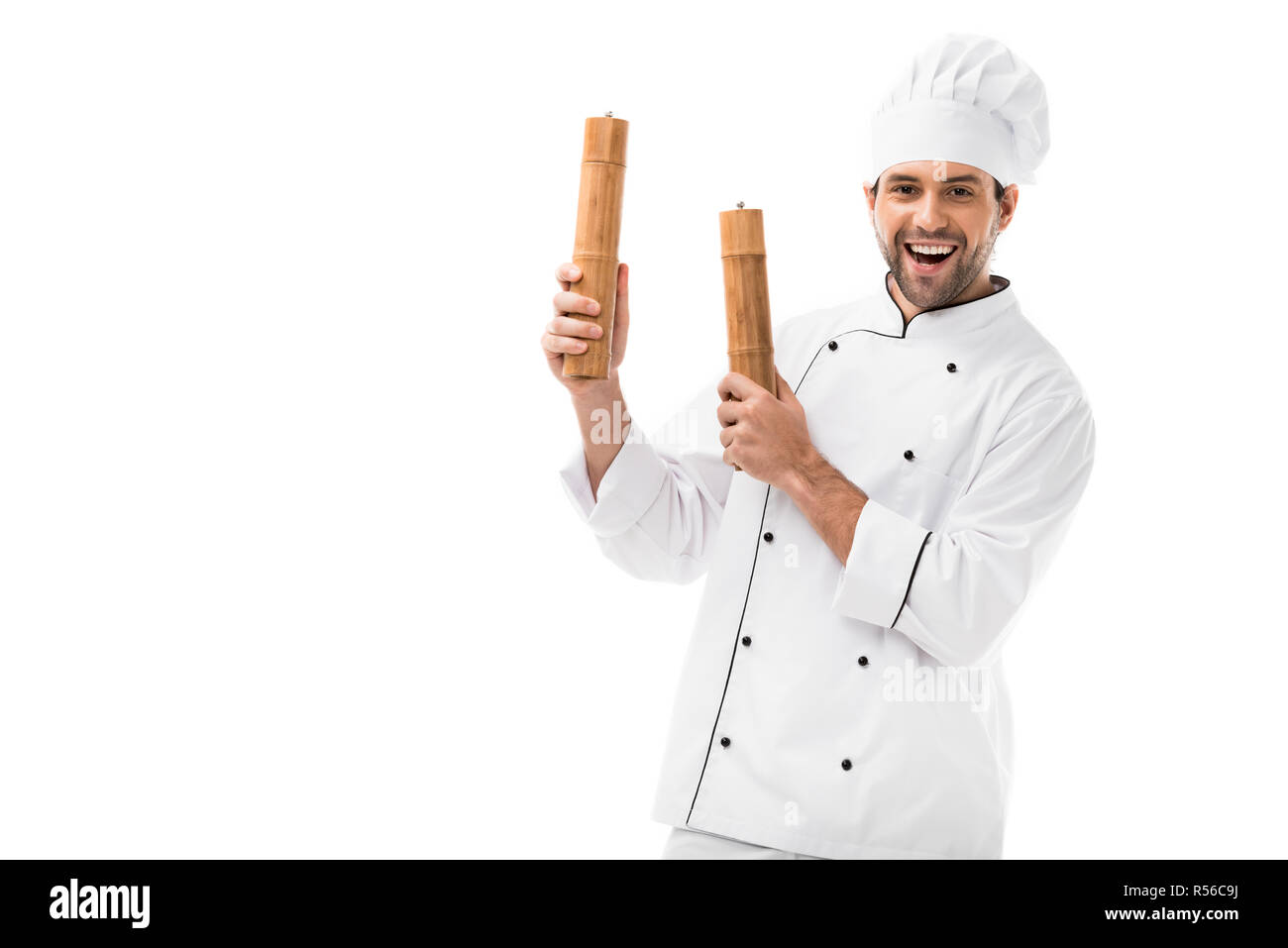 happy young chef holding bamboo pepper mills isolated on white - Stock Image