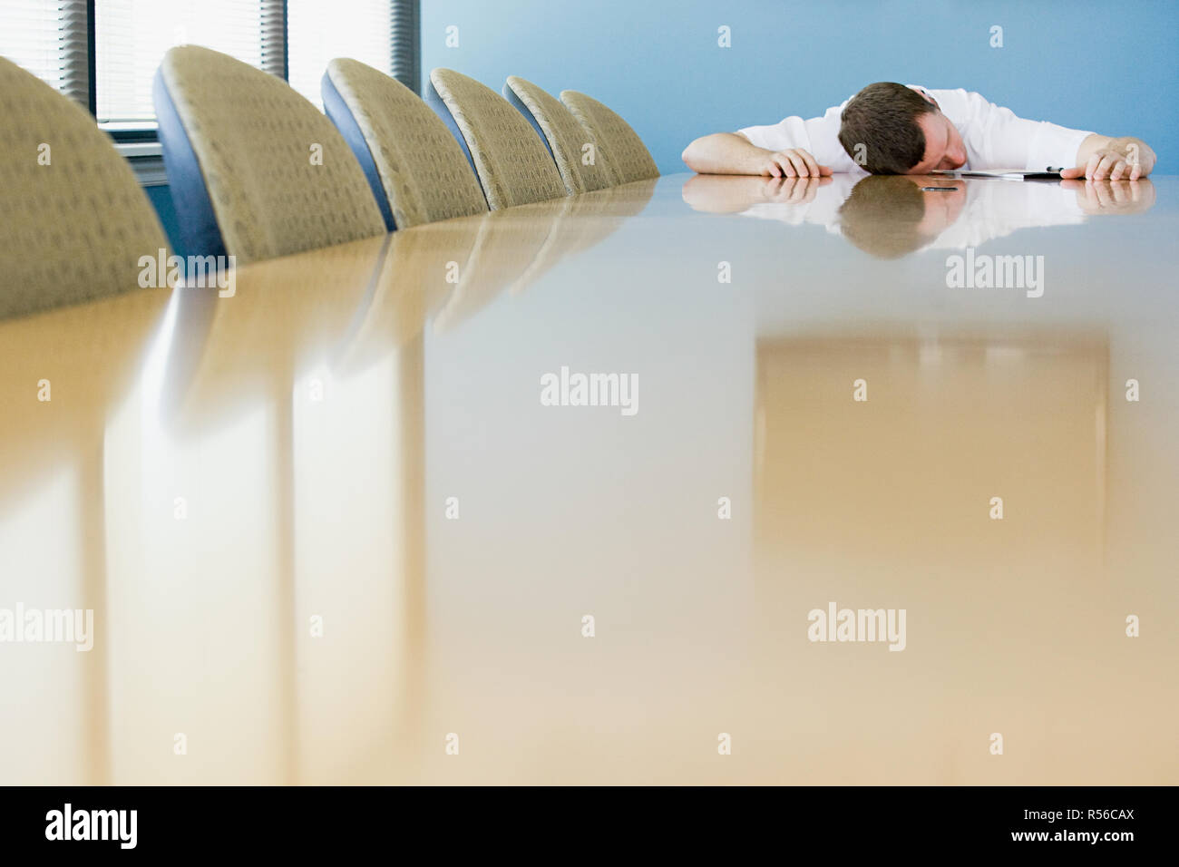 Man sleeping on conference table - Stock Image