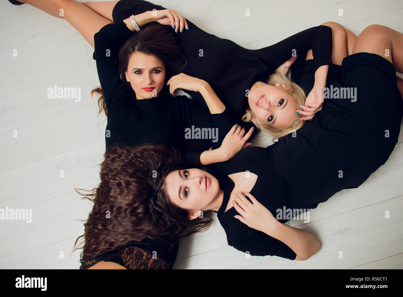 Three girl friends with suckers smiling lie. - Stock Image