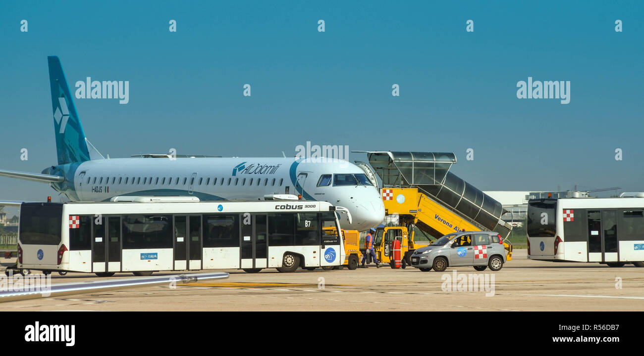 Air Dolomiti jet at Verona airport, Italy. An airport transfer bus is parked alongside. - Stock Image
