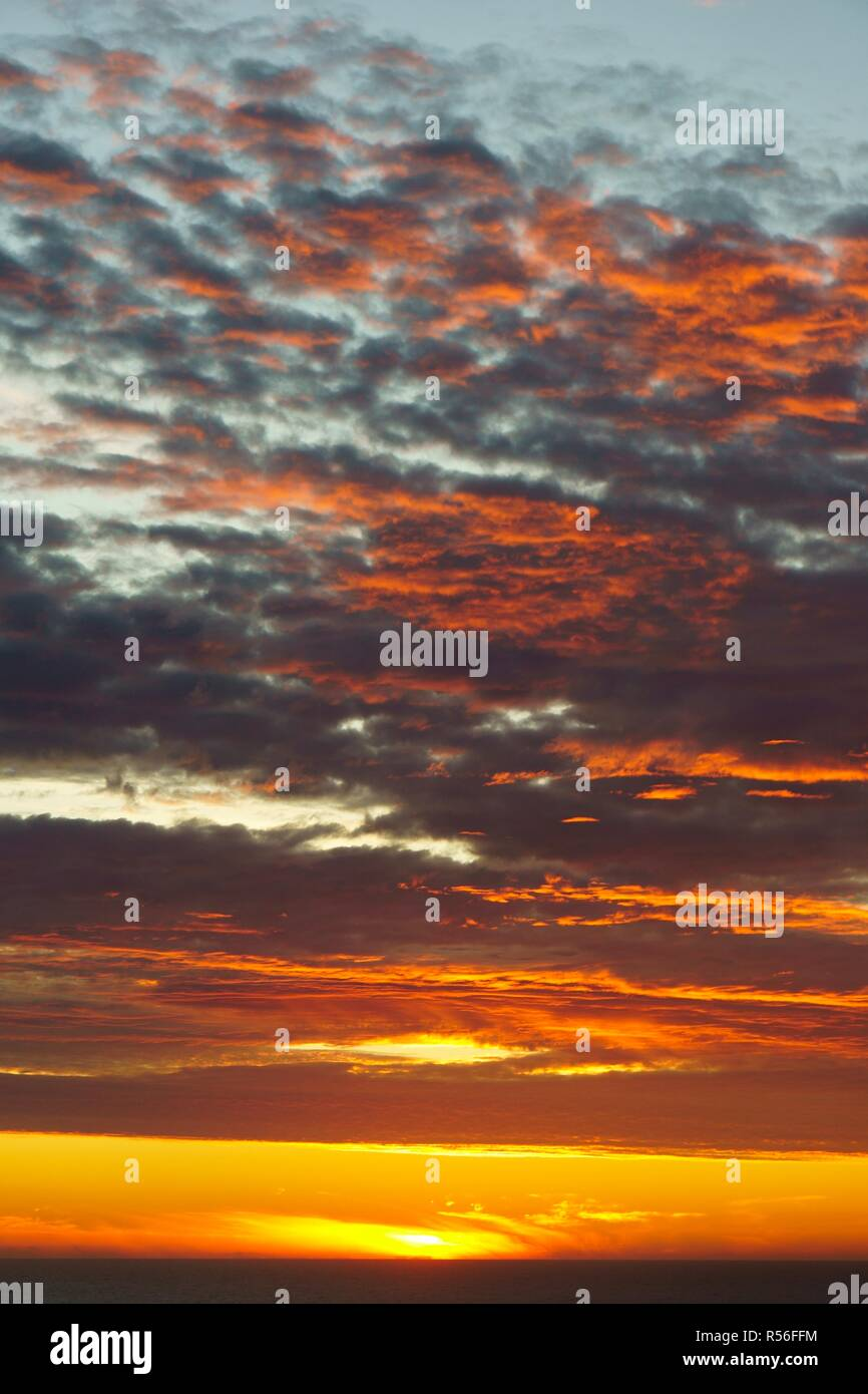 Shining sky over the Pacific Ocean at sunset, Chiloé Island, Chile - Stock Image