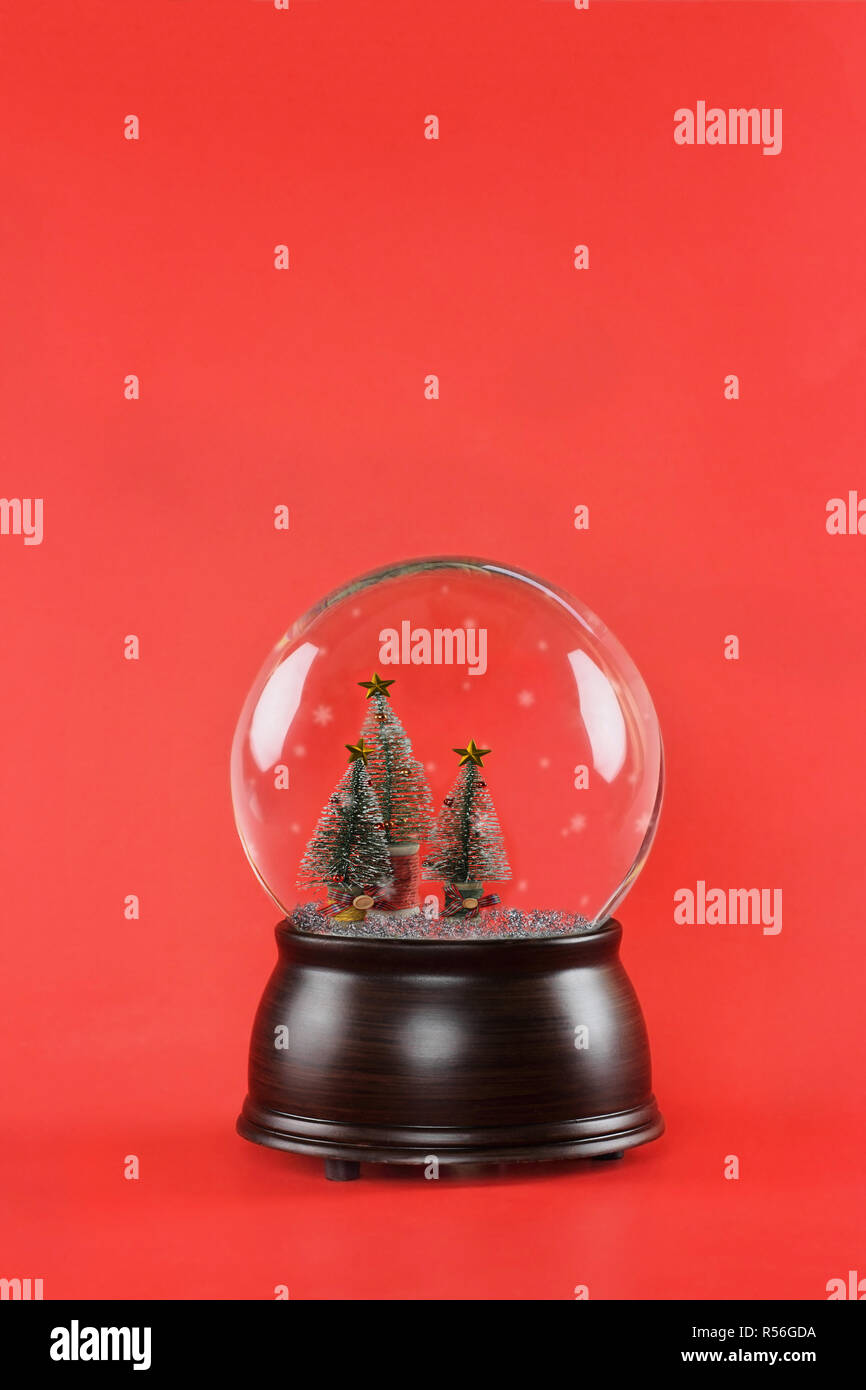 Christmas snow globe with wooden base and bottle brush Christmas trees against a red background. Free copy space for text available. - Stock Image