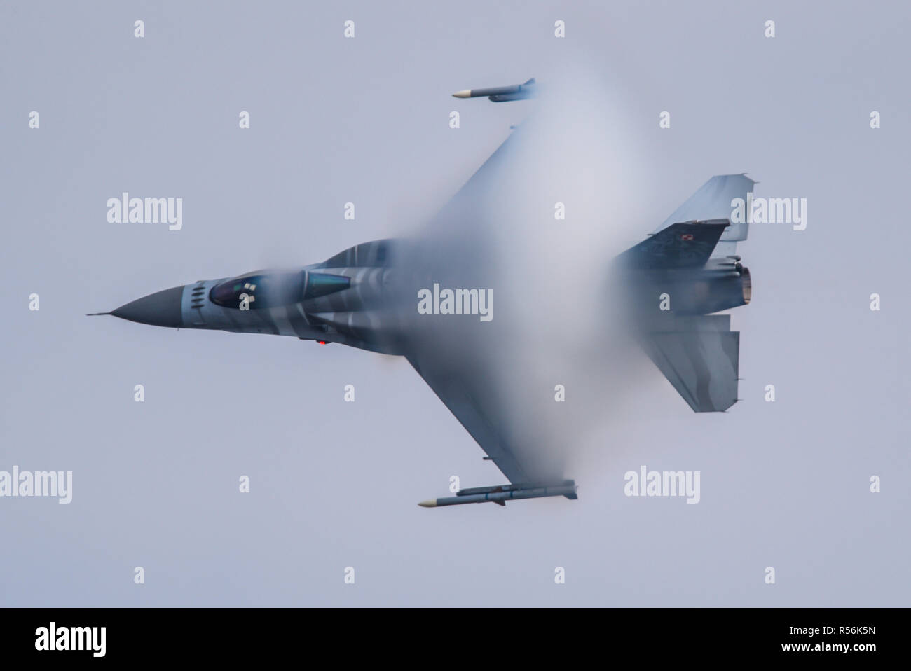 Polish Air Force Lockheed F-16 fighter jet plane creating a vapor cone shock cone at high speed at Royal International Air Tattoo, RIAT 2018, Fairford - Stock Image