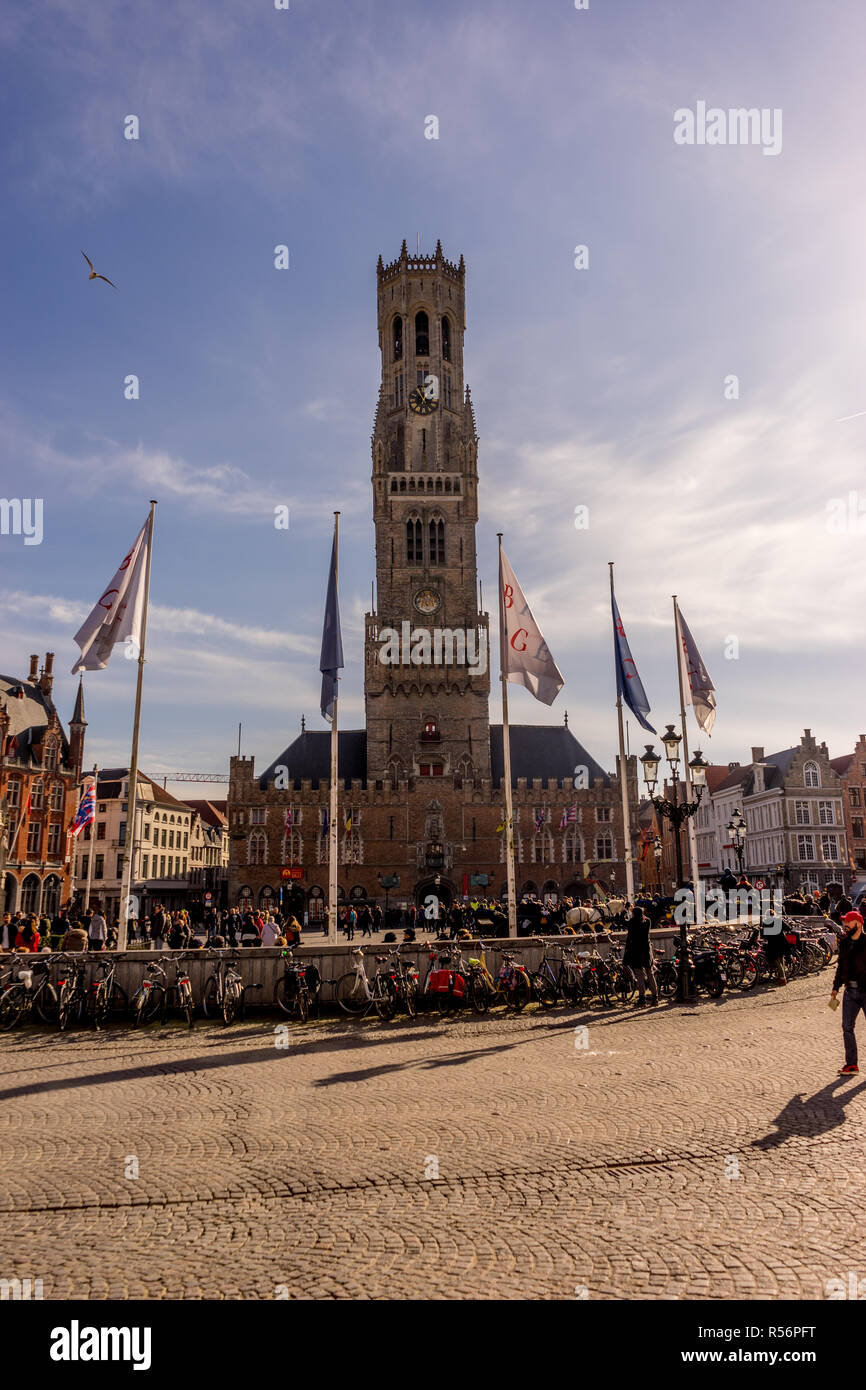 Bruges, Belgium - 17 February 2018: Belfry of Bruges, a group of people walking in front of a clock tower with Belfry of Bruges in the background Stock Photo